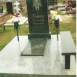 Памятник из черного гранита с лавкой из гранита и коваными вазами